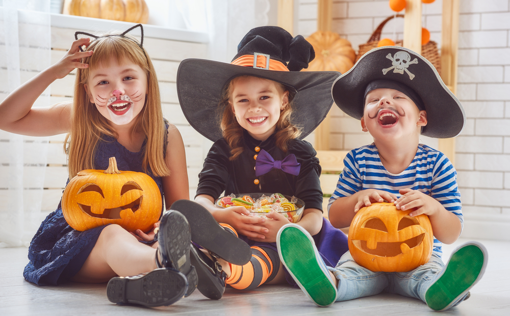 Three kids dressed in Halloween costumes.