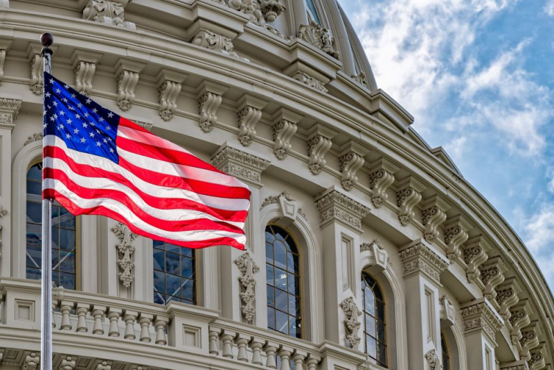 An American Flag waving in front of the Capitol Building.